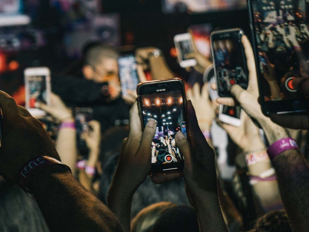 People recording concert with phones